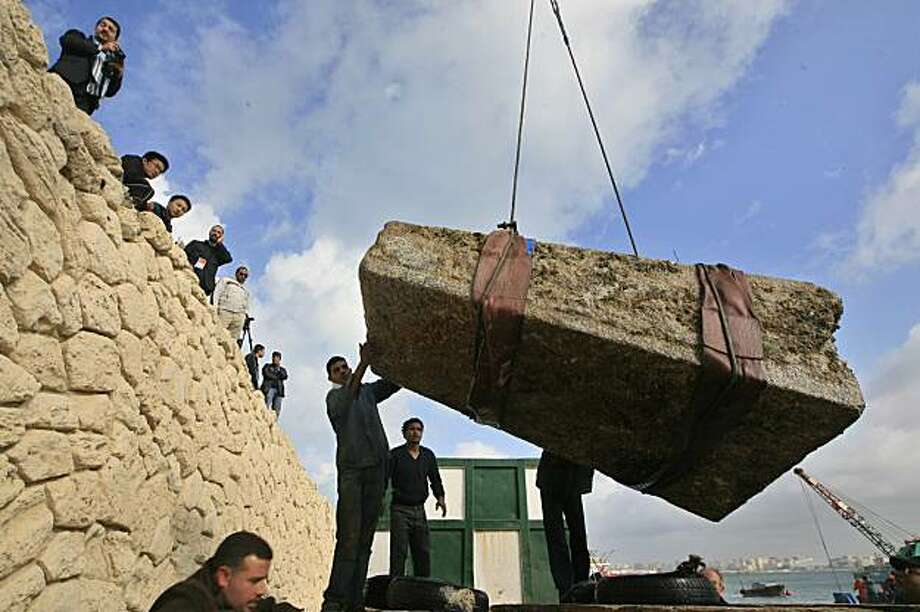 A huge granite block, part of a stone pillar from a temple in a sunken Cleopatra-era city off Alexandria, is lifted by a crane from the Mediterranean sea off the Egyptian port city on December 17, 2009. The nine-tonne stone block was part of a temple to Isis, ancient Egypt's goddess of fertility, near the underwater ruins of a palace reputed to have belonged to the famed queen, who ruled in the first century BC. TOPSHOTS/AFP PHOTO/KHALED DESOUKI (Photo credit should read KHALED DESOUKI/AFP/Getty Images) Photo: Khaled Desouki, AFP/Getty Images