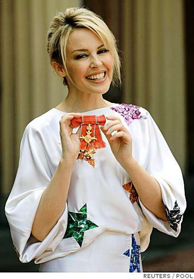 Australian singer Kylie Minogue smiles as she poses for photographers with the OBE she received from Britain's Prince Charles for her services to music at Buckingham Palace in London July 3, 2008.      REUTERS/Steffan Rousseau/Pool   (BRITAIN) Photo: POOL, REUTERS
