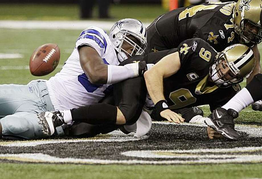 New Orleans Saints quarterback Drew Brees fumbles in the closing seconds under pressure from Dallas Cowboys running back Marion Barber in an NFL football game, Saturday, Dec. 19, 2009, in New Orleans.  Dallas won 24-17.  (AP Photo/Jim Dietz) Photo: Jim Dietz, AP