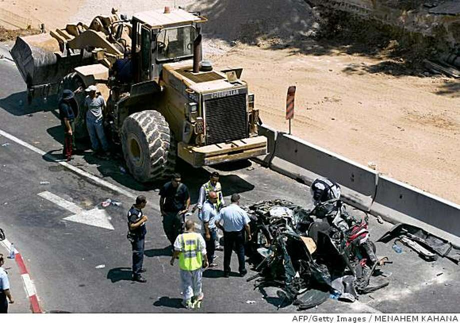 Israeli police inspect a car that was destroyed in an attack by a Palestinian man driving a bulldozer on Jaffa Road in Jerusalem on July 2, 2008.  A Palestinian man killed at least three people and wounded 30 more when he rammed a bulldozer into a bus and cars in central Jerusalem today before being shot dead, medics and police said. AFP PHOTO/MENAHEM KAHANA (Photo credit should read MENAHEM KAHANA/AFP/Getty Images) Photo: MENAHEM KAHANA, AFP/Getty Images