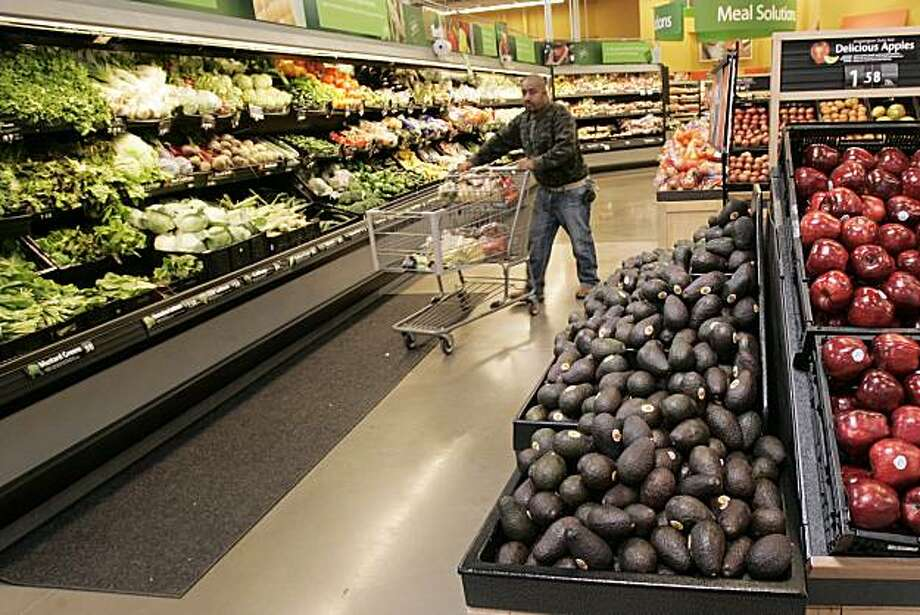 In this April 29, 2008, photo, a man pushes a shopping cart down a produce aisle at a Maumelle, Ark., Wal-Mart Supercenter store. Wal-Mart Stores Inc. on Tuesday, July 1, 2008 unveiled a new Web site noting their efforts to provide locally grown produce at its stores across the nation. The Bentonville-based retailer says the effort also helps cut down on mileage delivering the goods to stores. (AP Photo/Danny Johnston) Photo: Danny Johnston, AP