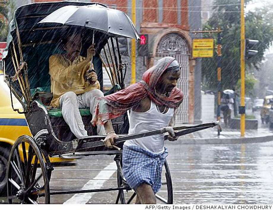 An Indian commuter rides a hand pulled rickshaw during a rainfall in Kolkata, on June 17, 2008.  An overnight rainfall flooded streets of the city and caused massive traffic disruptions, as flash floods and mudslides unleashed by heavy monsoon rains have claimed 25 lives and displaced 200,000 people in northeastern India, officials said.         AFP PHOTO/Deshakalyan CHOWDHURY (Photo credit should read DESHAKALYAN CHOWDHURY/AFP/Getty Images) Photo: DESHAKALYAN CHOWDHURY, AFP/Getty Images