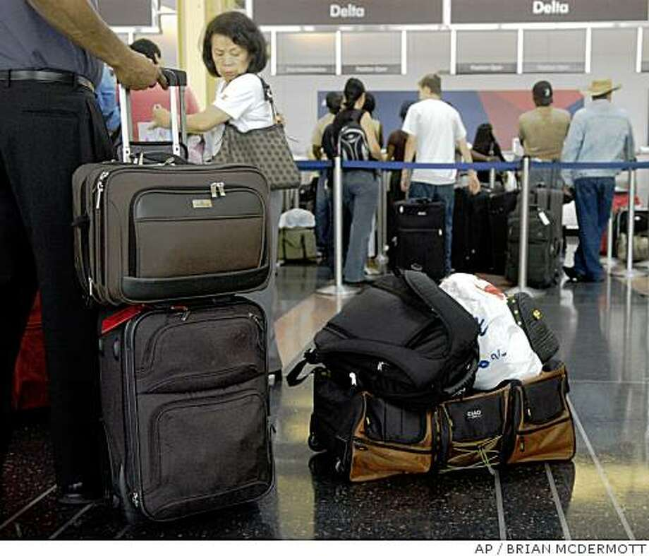 Customers wait in line with their luggage to check in for Delta flights at Reagan National Airport in Arlington, Va., on June 14, 2008. If you're flying American Airlines be prepared to pay that $15 first checked bag fee as the carrier deals with higher fuel prices. (AP Photo / Brian McDermott) Photo: BRIAN MCDERMOTT, AP