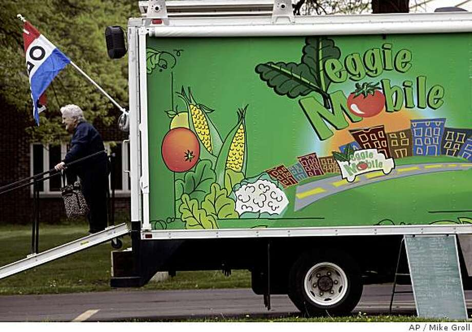 **APN ADVANCE FOR SUNDAY JULY 6**  A customer leaves the Veggie Mobile after buying produce in Albany, N.Y., Friday, May 9, 2008.   With the rapidly climbing cost of food and fuel, states and nonprofit groups are finding ways to get healthy food to underserved areas.  (AP Photo/Mike Groll) Photo: Mike Groll, AP