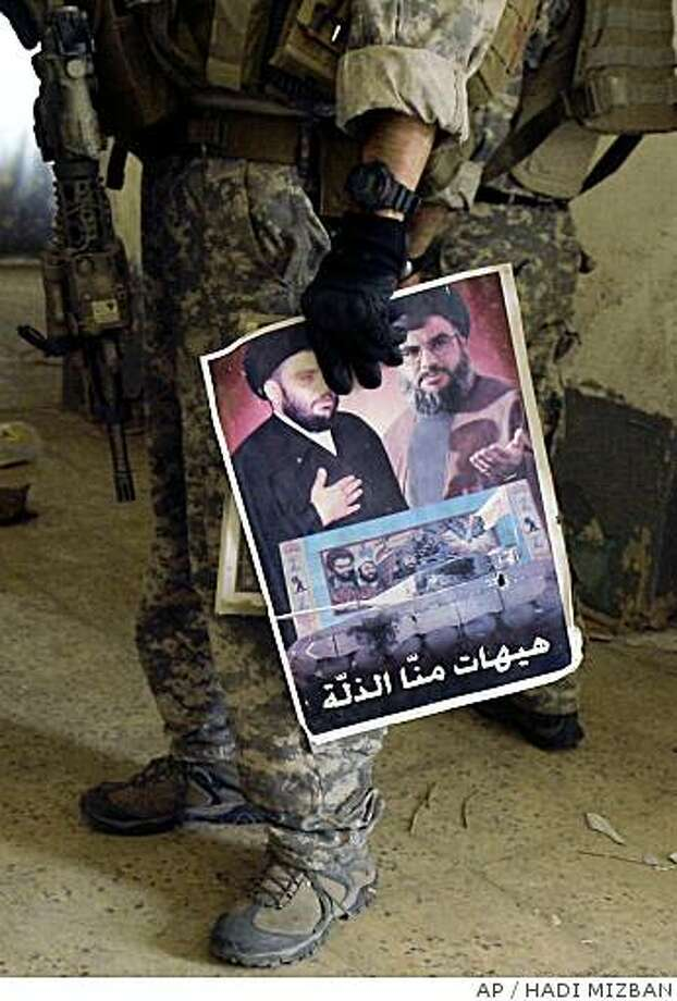 ** FILE ** In this June 20, 2008 file photo, a U.S. soldier holds a poster that shows the anti-U.S. cleric Muqtada al-Sadr, left, and the leader of Hezbollah, Sheik Hassan Nasrallah, during a search operation in Maysan province near the border with Iran, 320 kilometers, 200 miles, southeast of Baghdad, Iraq. Hezbollah instructors trained Shiite militiamen at remote camps in southern Iraq until three months ago when they slipped across the border to Iran, presumably to continue instruction on Iranian soil, according to two Shiite lawmakers and a top army officer.(AP Photo/Hadi Mizban) Photo: HADI MIZBAN, AP