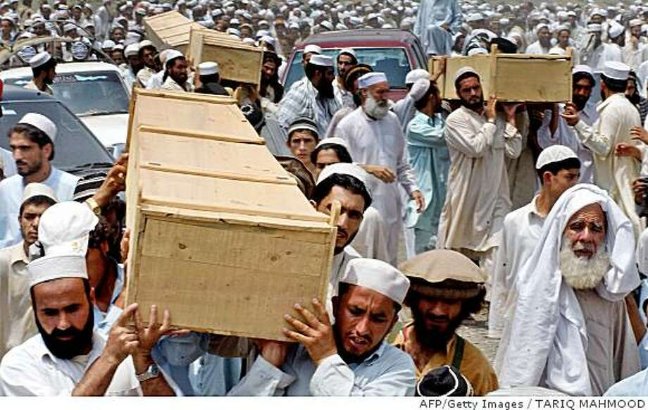 Pakistani tribesmen carry coffins during a funeral ceremony in Par Qambarkhel area of Khyber tribal district on June 30, 2008, after the deaths of six people in an attack by troops on the home of a militant. An explosion ripped through the house of a leading Pakistani militant on 30 June, killing six people, as troops extended an anti-insurgent offensive in the Khyber tribal district. AFP PHOTO/Tariq MAHMOOD (Photo credit should read TARIQ MAHMOOD/AFP/Getty Images) Photo: TARIQ MAHMOOD, AFP/Getty Images