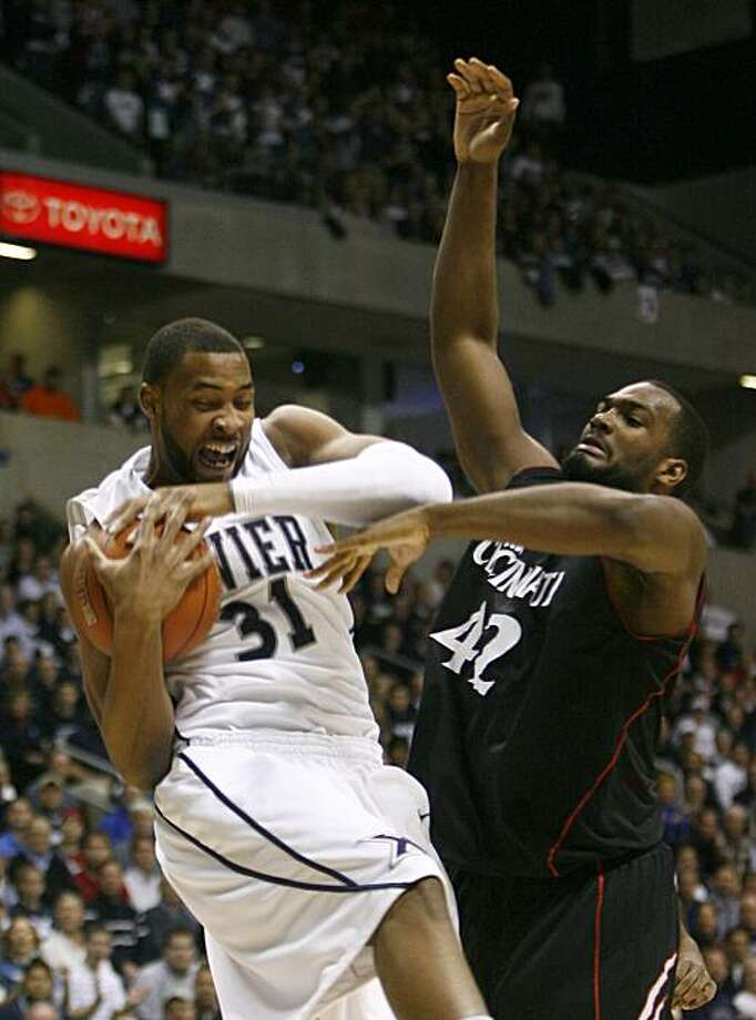 Xavier forward Jason Love (31) and Cincinnati's Steve Toyloy (42) go for the ball in the first half during an NCAA college basketball game, Sunday, Dec. 13, 2009, in Cincinnati.  (AP Photo/David Kohl) Photo: David Kohl, AP