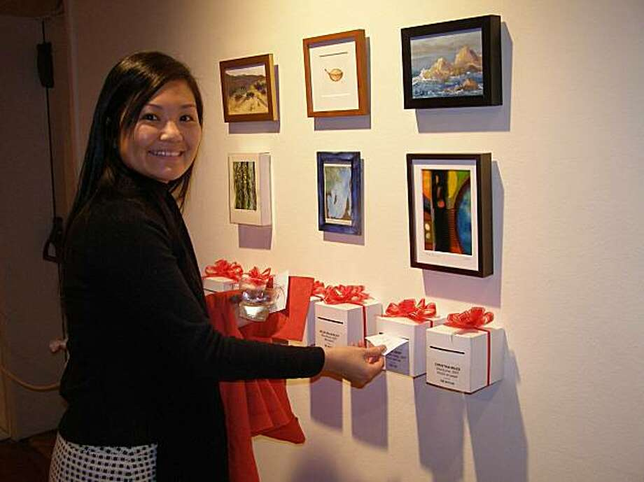 "A patron at the 2007 ""Miniatures"" exhibition at the Monterey Museum of Art enters the raffle for her preferred work. Photo: Monterey Museum Of Art"