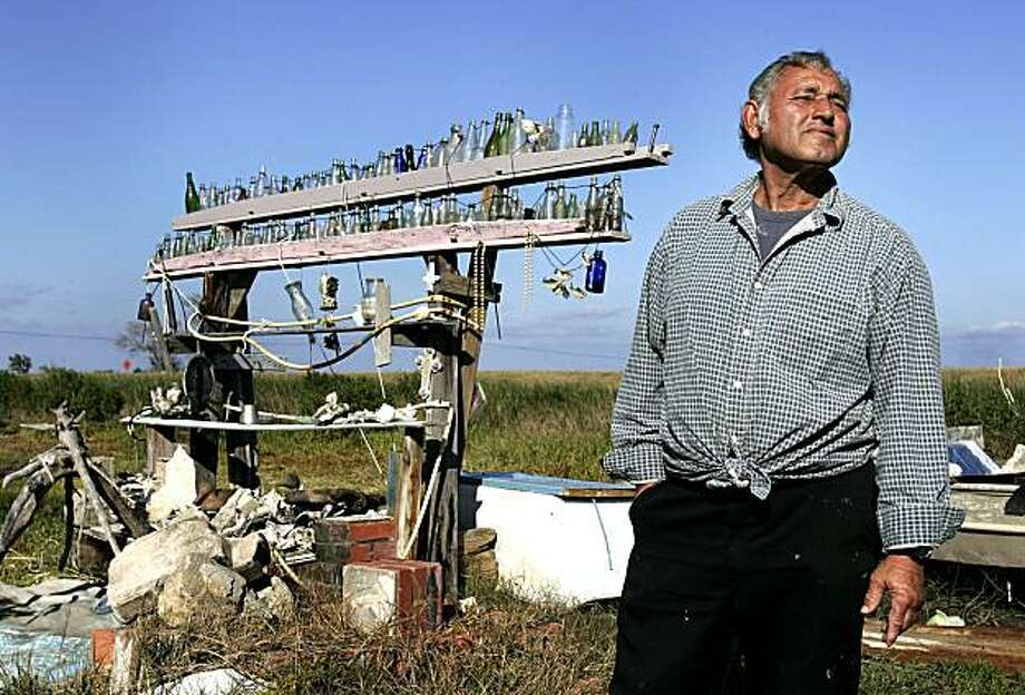 **ADVANCE FOR MONDAY, DEC. 14** This Nov. 23, 2009 photo shows Edison Dardar standing near his bottle collection in his backyard on Isle de Jean Charles, La., Monday, Nov. 23, 2009. Holdouts in the hurricane-damaged Indian village refuse to give in to urges from a tribal chief, scientists and public officials to relocate inland, despite frequent floods and disappearing marshland that brings the Gulf of Mexico closer every year. (AP Photo/Patrick Semansky) Photo: Patrick Semansky, AP