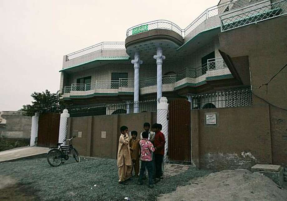 Pakistani children play in front of a house where police reportedly arrested five American Muslims in Sargodha, Pakistan, Thursday, Dec. 10, 2009. Five young American Muslims arrested in Pakistan met with representatives of an al-Qaida linked group and asked for training but were turned down because they lacked references from trusted militants, a Pakistani law enforcement official said Thursday. (AP Photo/K.M. Chaudary) Photo: K.M. Chaudary, AP