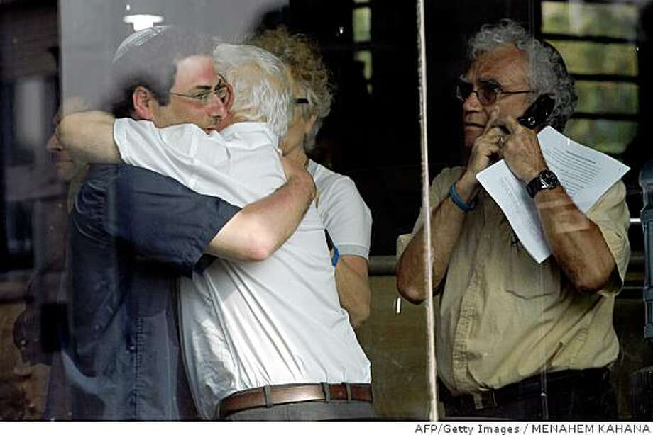 Ofir Regev (L), the brother of Israeli soldier Eldad Regev kidnapped by Lebanon's Hezbollah, hugs an unidentified person as his father Tzvi Regev (R) looks on speaking on the telephone following a meeting with Prime Minister Ehud Olmert's in his Jerusalem office on June 29, 2008. The Israeli cabinet gave its green light today for a prisoner exchange with Hezbollah, even though two soldiers captured by the Lebanese militia two years ago are known to be dead. AFP PHOTO/MENAHEM KAHANA (Photo credit should read MENAHEM KAHANA/AFP/Getty Images) Photo: MENAHEM KAHANA, AFP/Getty Images