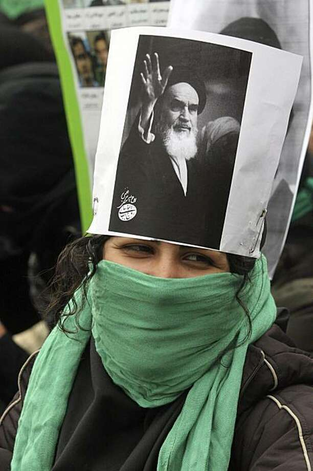 This photo, taken by an individual not employed by the Associated Press and obtained by the AP outside Iran, shows an anti-government and pro-reform Iranian female student displaying a poster of the late revolutionary founder Ayatollah Khomeini, as she covers her face to avoid to be identified by security,  during a demonstration saying the clip on burning of picture of Ayatollah Khomeini shown by state TV was fabricated, at the Tehran University campus in Tehran, Iran, Sunday, Dec. 13, 2009. State television cameras caught images of alleged students tearing up and burning Khomeini's photo apparently during anti-government protests last week and the images have been repeatedly broadcast on TV. The opposition maintains those were isolated incidents used by the regime to discredit the reformists, who are protesting what they say were rigged presidential elections in June. Khomeini remains widely respected and revered in Iran. (AP Photo) EDITORS NOTE AS A RESULT OF AN OFFICIAL IRANIAN GOVERNMENT BAN ON FOREIGN MEDIA COVERING SOME EVENTS IN IRAN, THE AP WAS PREVENTED FROM INDEPENDENT ACCESS TO THIS EVENT Photo: AP