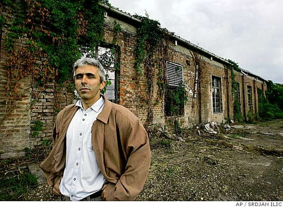 "**APN ADVANCE FOR SUNDAY JUNE 29** Jovica Stevic, vice president of Serb-German Cooperation Society is seen in barracks complex used for prison camp are seen Friday, June 13 2008 in Sremska Mitrovica, some 80 km (50 miles) north of Belgrade. After World War II, the sprawling complex on the outskirts of this northern Serbian town, served as a prison camp for local Germans, where about 2,000 people died. ""About 52,000 German civilians, mostly children, perished in various camps in Yugoslavia between 1945-47,"" said Hans Supritz, president of the Association of Danube Swabians in Germany. When Serbian entrepreneur Mitar Tasovac purchased a long-abandoned factory intending to develop a housing complex on the site, he uncovered a chilling chapter of local history that had laid dormant for sixty years. (AP Photo/Srdjan Ilic) Photo: SRDJAN ILIC, AP"