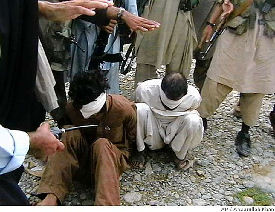 Pakistani Taliban get ready to execute two Afghans for their alleged spying for U.S. forces and helping orchestrate a suspected American missile strike that killed  14 people in a border village last month, Friday, In Khar in Pakistani tribal area of Bajour. (AP Photo/Anwarullah Khan) Photo: Anwarullah Khan, AP