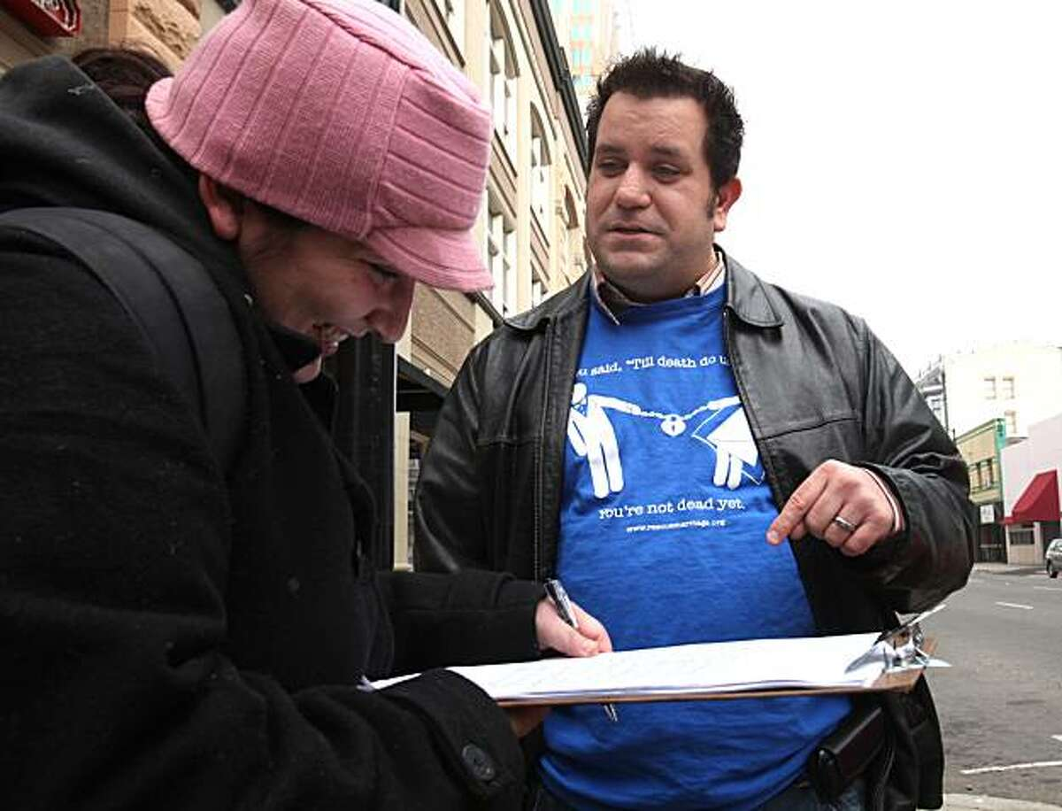 In this photo taken Saturday, Nov. 21, 2009, John Marcotte discusses his proposed ballot initiative to ban divorce as Cynthia Keagy, left, signs his petition to get measure on the ballot, in Sacramento, Calif. Marcotte is using the state's voter initiative process to make a satirical statement about the fight over gay marriage and voter approved 2008 Proposition 8 that banned gay marriage. (AP Photo/Rich Pedroncelli)