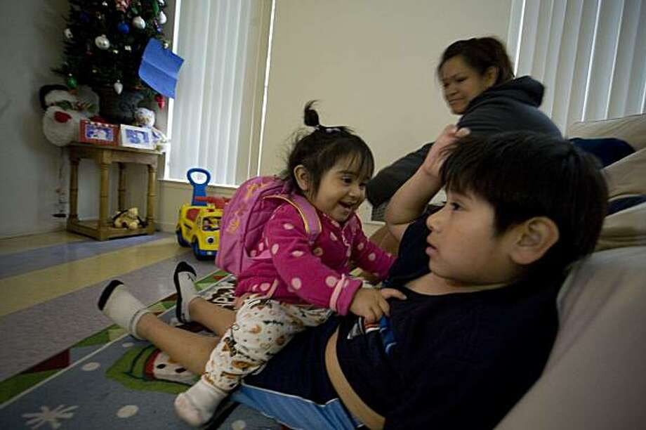Stephanie Osorio, 18 mos., left, jumps on her six-year-old brother, Luis Osorio's lap to play in front of the family's Christmas tree at home in San Francisco, Calif. on Sunday, December 13, 2009.  In the background, the children's mother, Alma Jimenez, stays at home with the kids while her husband, Erick Osorio (not pictured) is out looking for work. Kat Wade / Special to the Chronicle Photo: Kat Wade, Special To The Chronicle