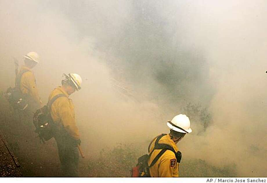 Fire crews from a joint task force from Nebraska, Colorado, Oregon and Kansas, are engufed by smoke from a wildfire as it approaches a home on Partington Ridge  Rd. south of Big Sur, Calif., Friday, June 27, 2008. Fire crews continue to fight the Basin Complex fire, which is burning in the Los Padres National Forest near the coastal town of Big Sur. (AP Photo/Marcio Jose Sanchez) Photo: Marcio Jose Sanchez, AP