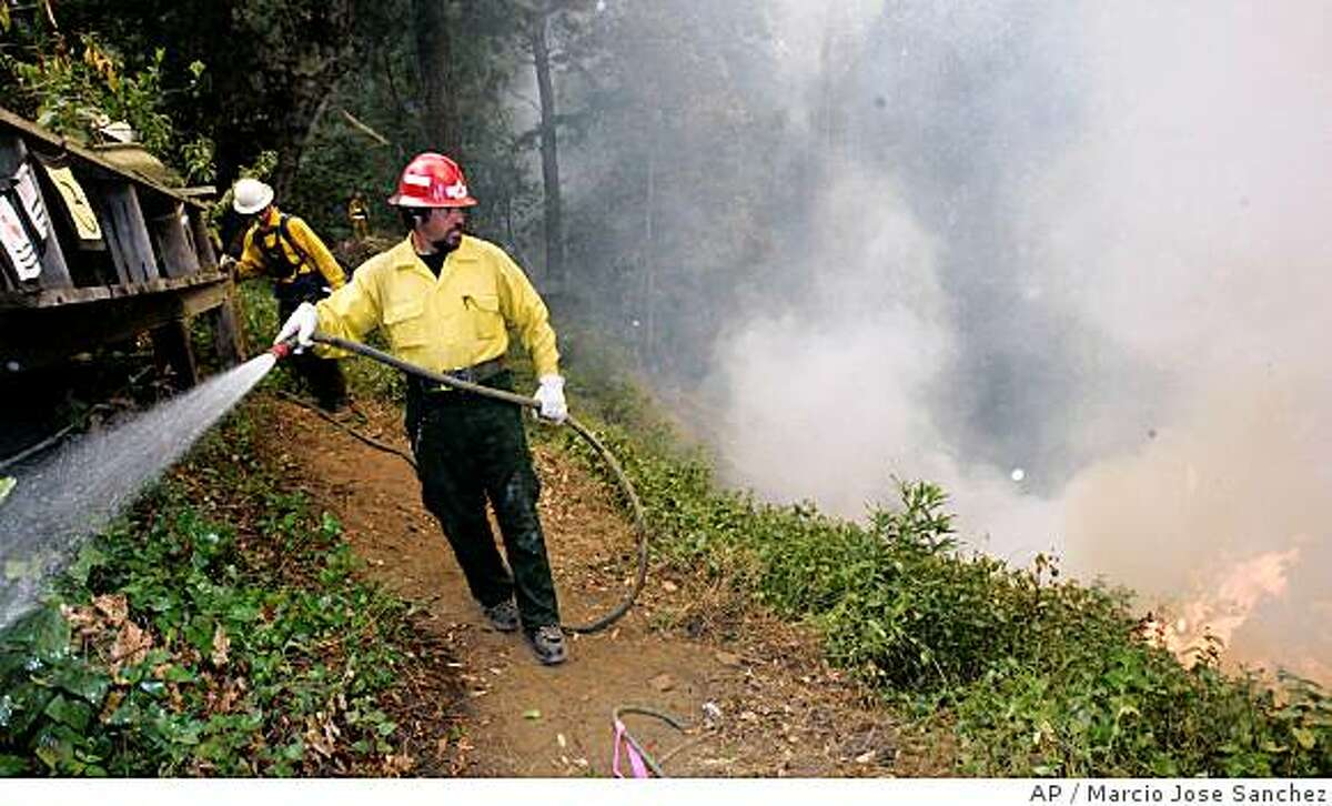 Robert Koch, with hose, of PatRick Corporation, a private contractor from Oregon, hoses down a house as a wildfire approaches on Partington Ridge Rd. South of Big Sur, Calif., Friday, June 27, 2008. Fire crews continue to fight the Basin Complex fire, which is burning in the Los Padres National Forest near the coastal town of Big Sur. (AP Photo/Marcio Jose Sanchez)