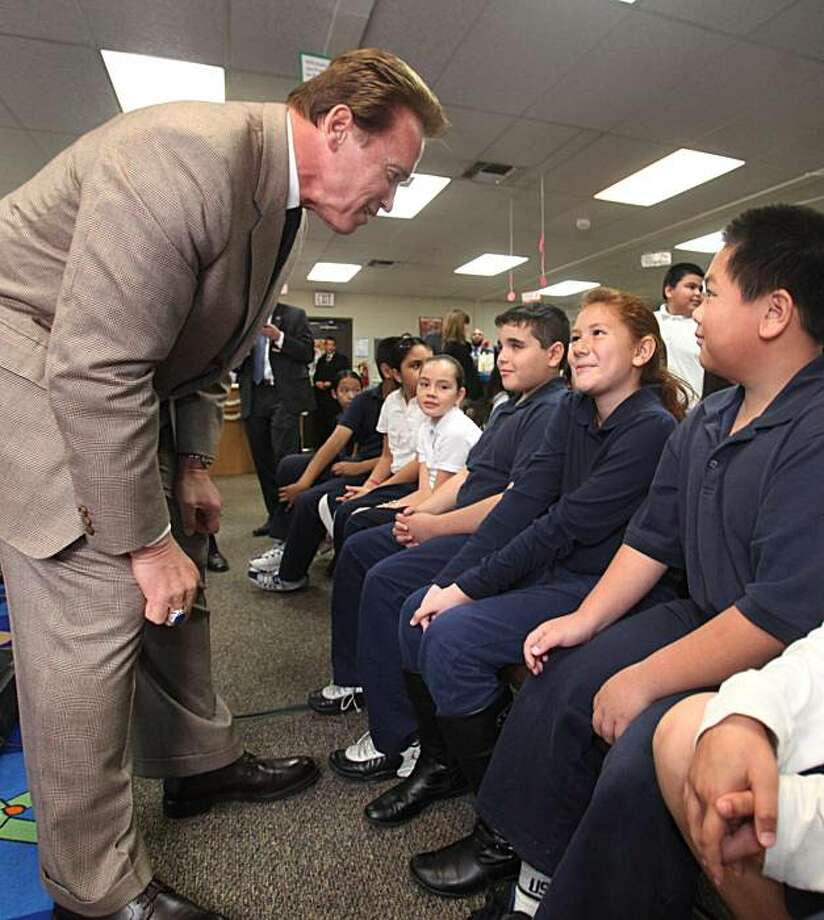Gov. Arnold Schwarzenegger talks with fifth-grader Emyly Lua, 10, after holding a news conference at Noralto Elementary School in Sacramento, Calif., Tuesday, Dec. 8, 2009.  Schwarzenegger visited the school where he called on the Legislature to approve a education reform package. (AP Photo/Rich Pedroncelli) Photo: Rich Pedroncelli, AP