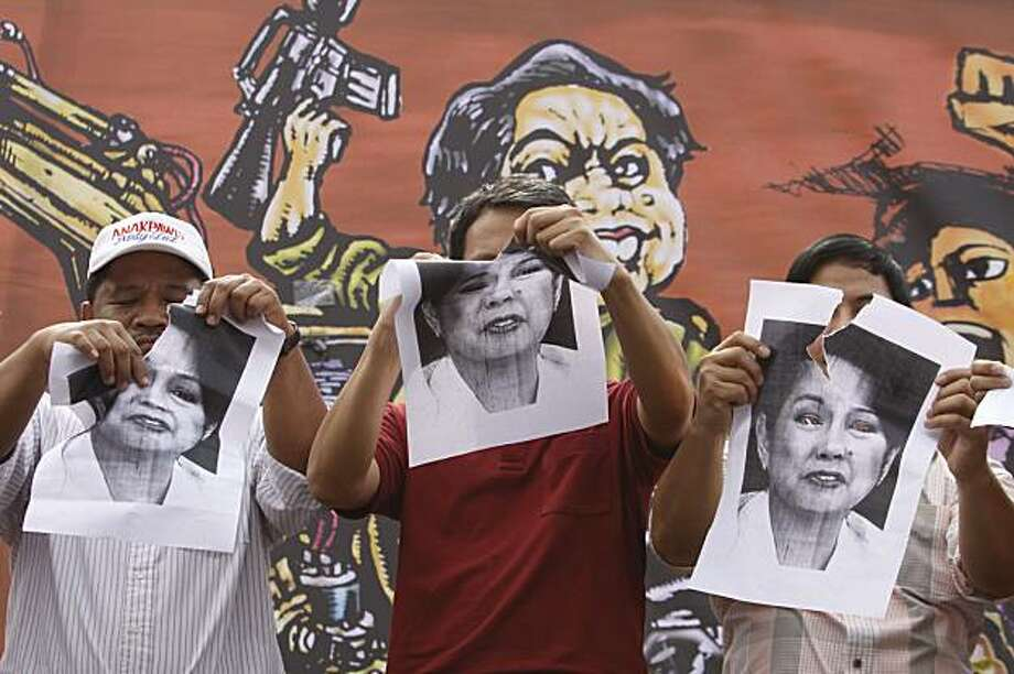 Militant leaders tear pictures of Philippine President Gloria Macapagal Arroyo during a rally calling for an end to martial law in southern Maguindanao province as they commemorate International Human Rights Day just outside the gates of Malacanang Presidential Palace in Manila, Philippines, Thursday, Dec. 10, 2009. Critics called it a dangerous precedent, but cabinet members said martial law was needed to stave off a rebellion by the powerful Ampatuan clan, the main suspects in the Nov. 23 killings of 57 people, and their thousands-strong private armies ready to fight the government. (AP Photo/Aaron Favila) Photo: Aaron Favila, AP