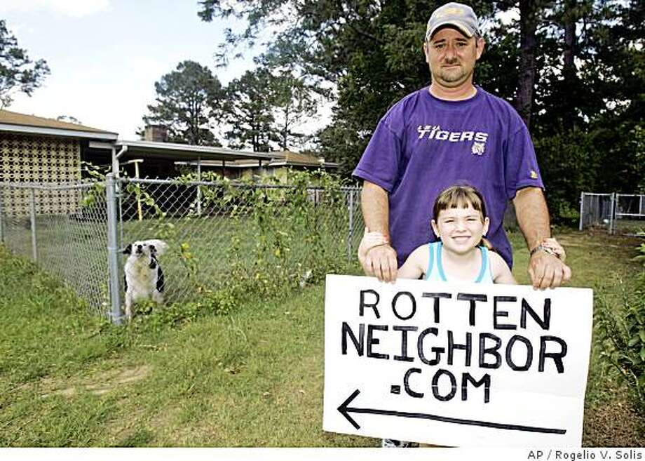 David Adams and his daughter Carly, 5, hold the sign they posted earlier this year between their home and that of their neighbor, whose two dogs they allege bark at all hours of the night, June 5, 2008, in Magnolia, Miss. Adams posted a video of the dogs barking on the Web site RottenNeighbor.com, which received several thousands of hits and comments. (AP Photo/Rogelio V. Solis) Photo: Rogelio V. Solis, AP