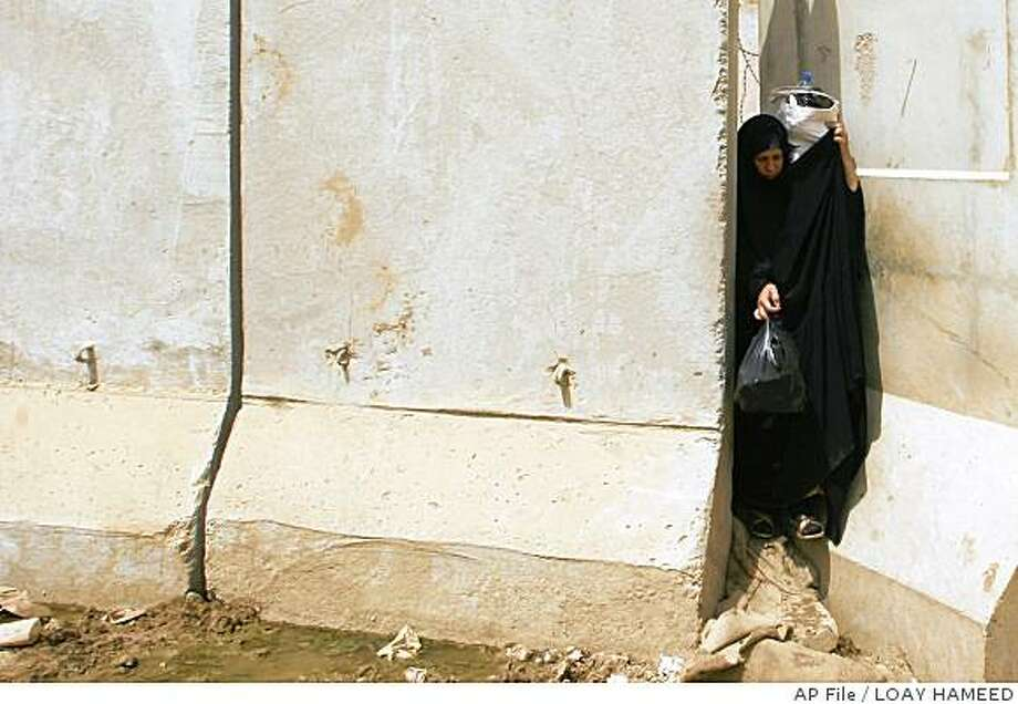 ** FILE I** An Iraqi woman tries to pass between concrete walls which separates a Shiite and a Sunni area in the Dora neighborhood if southern Baghdad, Iraq, in this Sunday, June 22, 2008 file photo. A unilateral cease-fire by a feared Shiite militia, the deployment of additional 30,000 U.S. troops and the defection of Sunni insurgents to join the U.S. military in the fight against al-Qaida are often cited as major contributing factors to the present lull in violence in the Iraqi capital. But, in no small part, Baghdad owes much of its peace to the endless row after row of walls that have been used to protect anything in the city from neighborhoods, hospitals, outdoor markets, schools and banks to the hundreds of security checkpoints across the city.(AP Photo/Loay Hameed, FILE) Photo: LOAY HAMEED, AP File