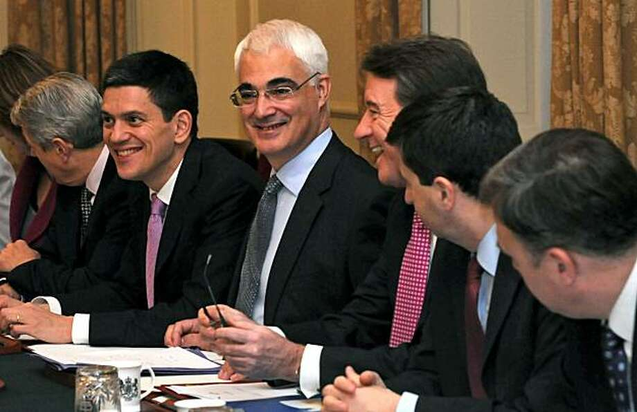 Britain's Treasury chief Alistair Darling, third left, talks with Business Secretary Peter Mandelson, third right, during a cabinet meeting at 10 Downing Street, London ahead of a pre-budget report Wednesday Dec. 9, 2009. Darling was widely expected to announce on Wednesday a tax on bank bonuses in his pre-budget statement, an updated plan for taxing and spending that a senior official warned would be painful. Darling has sharply criticized bonuses paid to bankers, especially at companies saved by taxpayers' money, and is under pressure to rein in spending to deal with a deficit of at least 175 billion pounds ($284 billion) this year. Foreign Secretary David Miliband is second left..  (AP Photo/ Anthony Devlin/PA Wire, Pool) Photo: Anthony Devlin, AP