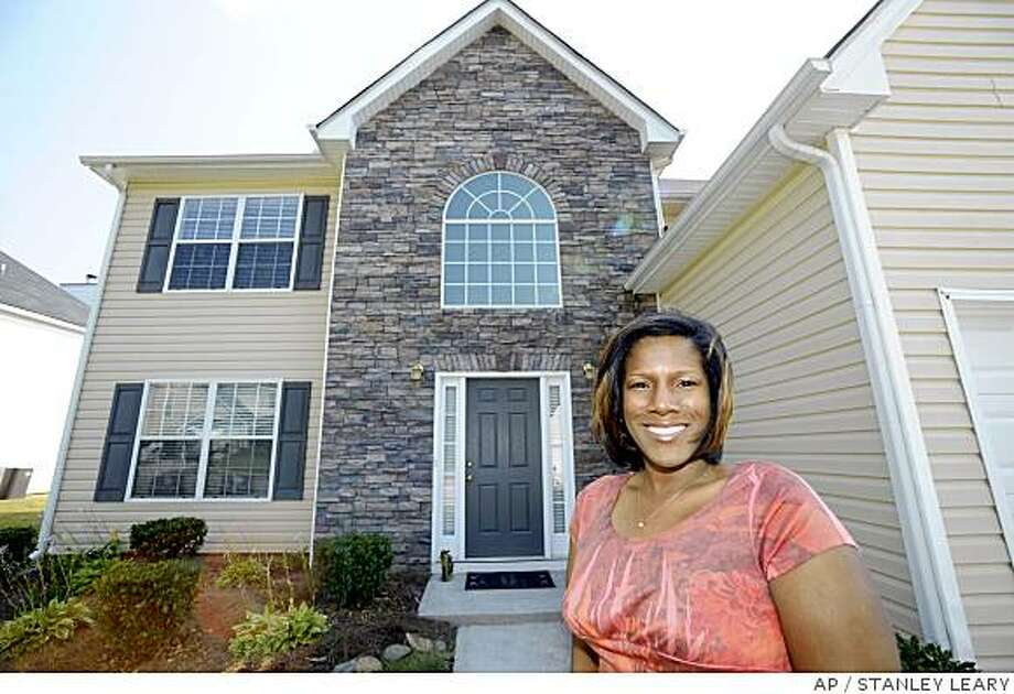 April Keels stands in front of her home in Covington, Ga on Wednesday, June 25, 2008.  Nearly four years ago, Keels bought a the four-bedroom home outside Atlanta for $160,000, with $5,000 in down-payment assistance arranged through Sacramento, Calif.-based Nehemiah Corp. of America. (AP Photo/Stanley Leary) Photo: STANLEY LEARY, AP