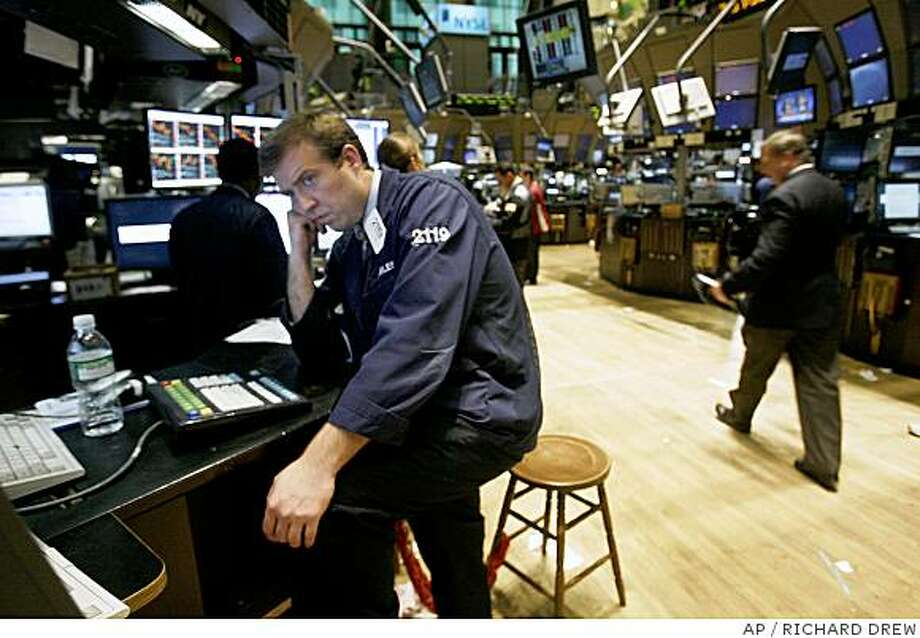Specialist Charles Janness watches his screens at his post on the New York Stock Exchange trading floor, Thursday June 26, 2008. Wall Street plunged Thursday, hurtling the Dow Jones industrials down to their lowest point in nearly two years as investors contended with a barrage of bad news: a surge in oil prices past $140 a barrel and warnings of trouble in the key financial, automotive and high-tech industries. (AP Photo/Richard Drew) Photo: RICHARD DREW, AP