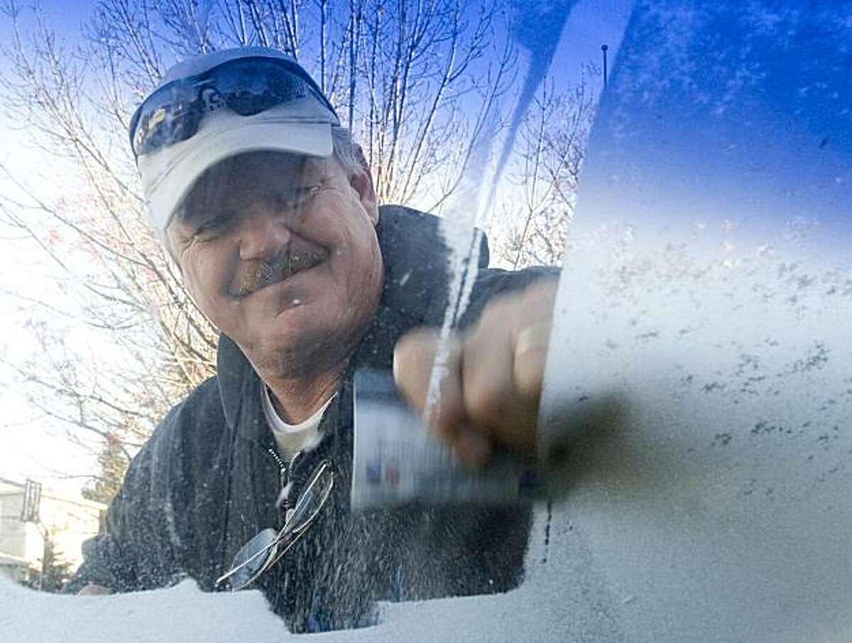 Gary Wagner, of Folsom, uses his credit card to remove heavy frost from the front window of his SUV while visiting relatives in Vacaville, Calif., Tuesday, Dec. 8, 2009. Temperatures in the area dropped into the low 20's overnight. (AP Photo/The Reporter, Rick Roach) MANDATORY CREDIT.