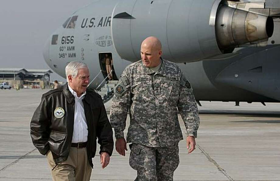 US Secretary of Defense Robert Gates (L) walks with US Army Lt. General Kenneth Hunzeker after arriving at Baghdad International Airport December 10, 2009 in Baghdad, Iraq. Secretary Gates stopped in Iraq following a two day trip to Afghanistan one week after US President Barack Obama announced that he will send an additional 30,000 troops to Afghanistan.  AFP PHOTO/Justin Sullivan/POOL (Photo credit should read JUSTIN SULLIVAN/AFP/Getty Images) Photo: Justin Sullivan, AFP/Getty Images