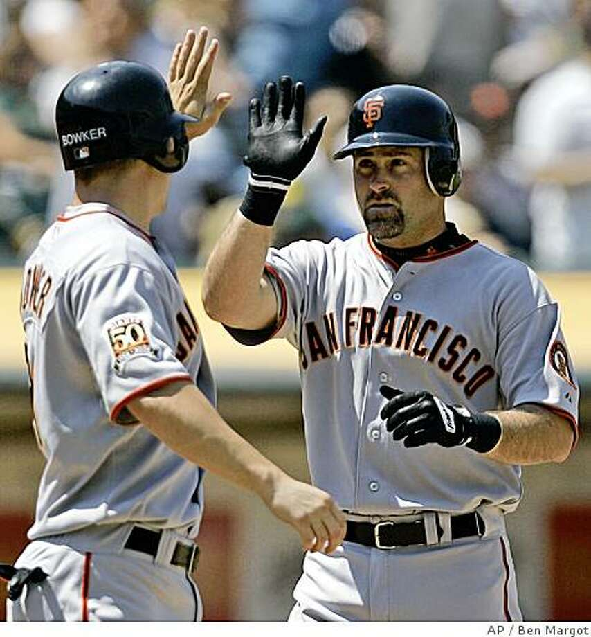 San Francisco Giants' Rich Aurilia, right, is congratulated by teammate John Bowker, left, after Aurilia hit a two-run home run off Oakland Athletics' Santiago Casilla during the seventh inning of a baseball game Sunday, June 29, 2008, in Oakland, Calif. (AP Photo/Ben Margot) Photo: Ben Margot, AP
