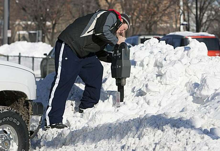 Nick Grobe of Oakland, Iowa, climbs a snow pile to feed a parking meter in downtown Omaha, Neb., Thursday, Dec. 10, 2009. A blast of cold air and wind followed the snowstorm that struck the midwest, and drove temperatures far below zero. (AP Photo/Nati Harnik) Photo: Nati Harnik, AP