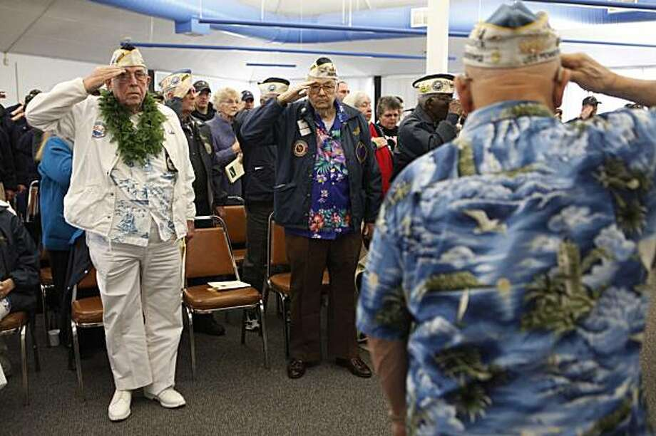 "68 years after the attack on Pearl Harbor, Members of the Pearl Harbor Survivors Association San Francisco Bay Area chapter 2,  John Rauschkolb, 88, and Bill Gertz, 89, salute at the start of a commemorative ceremony for the ""Day of Infamy"" survivors at the U.S. Coast Guard Support Command on Monday Dec. 07, 2009 in Alameda, Calif. Photo: Mike Kepka, The Chronicle"