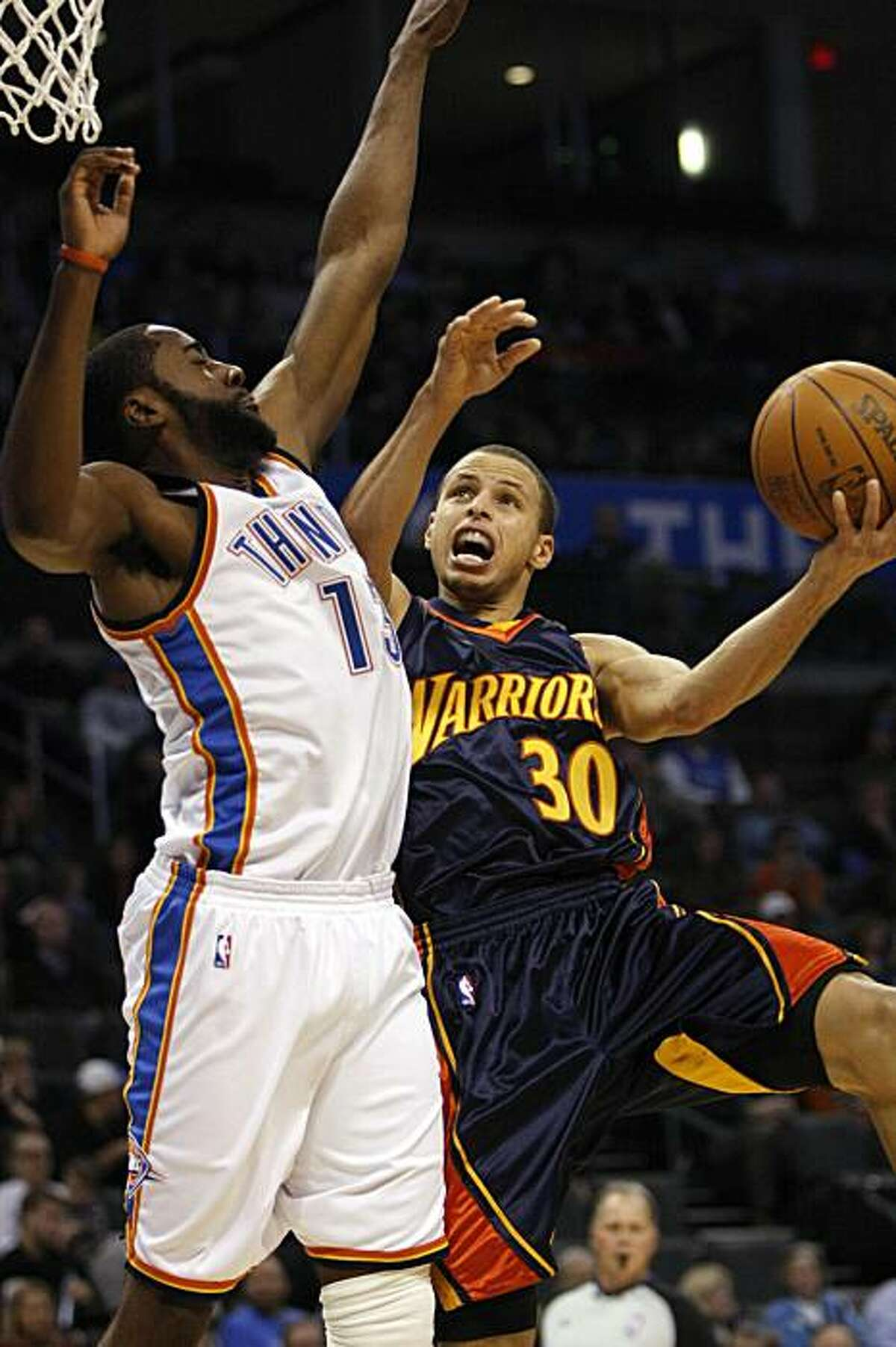 Golden State Warriors guard Stephen Curry goes up for a shot as Oklahoma City Thunder's James Harden defends in the first half in Oklahoma City on Monday.