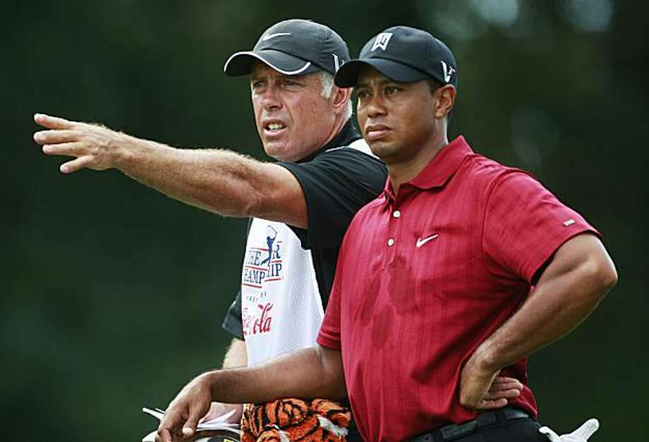 Tiger Woods gets some direction from his caddie Steve Williams on the fifth fairway during the final round of The Tour Championship golf tournament at East Lake Golf Club in Atlanta Sunday, Sept. 27, 2009. (AP Photo/Dave Martin) Photo: Dave Martin, AP