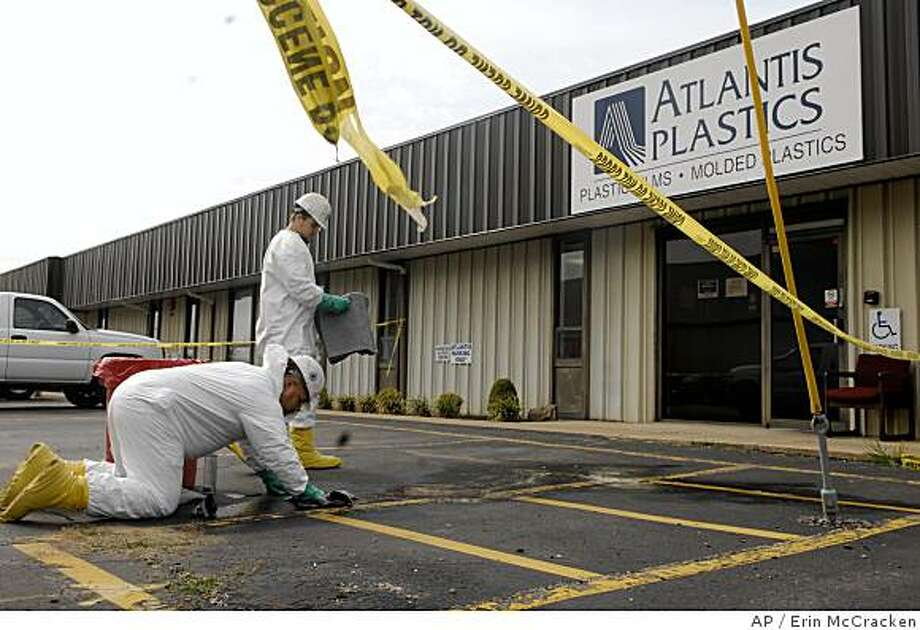 Workers with American Enviro-Services clean up an area surrounded by crime scene tape in front of the Atlantis Plastics plant in Henderson, Ky., where an employee shot and killed five people at the plant in Henderson before killing himself early Wednesday, June 25, 2008. (AP Photo / Evansville Courier & Press, Erin McCracken)**Mandatory Credit** Photo: Erin McCracken, AP