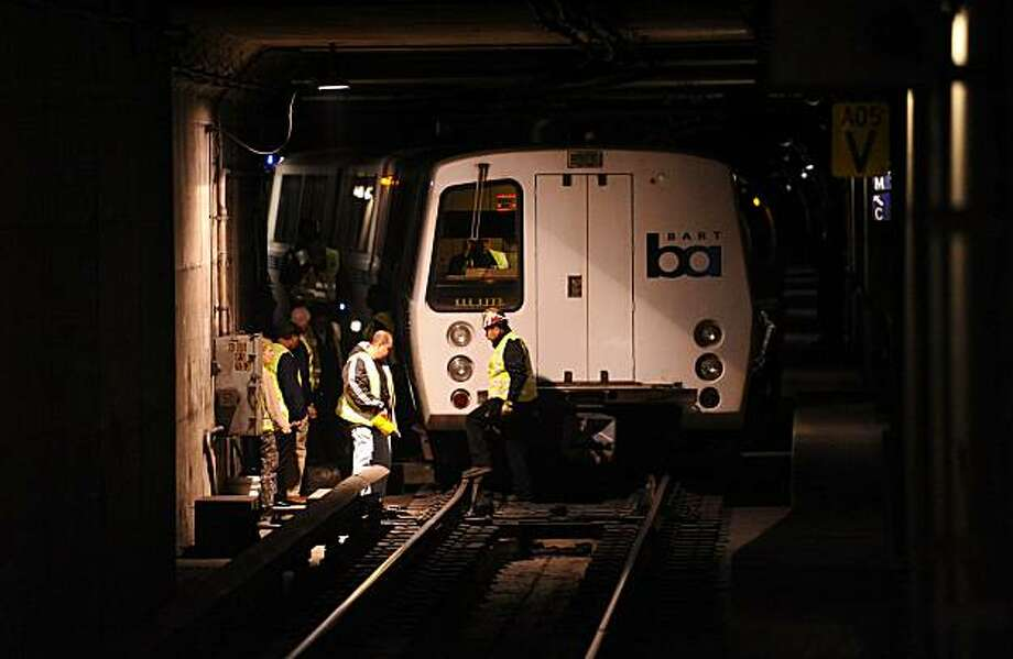 Investigators examine a derailed BART train on Wednesday at the 12th Street station in Oakland. Photo: Noah Berger, Special To The Chronicle