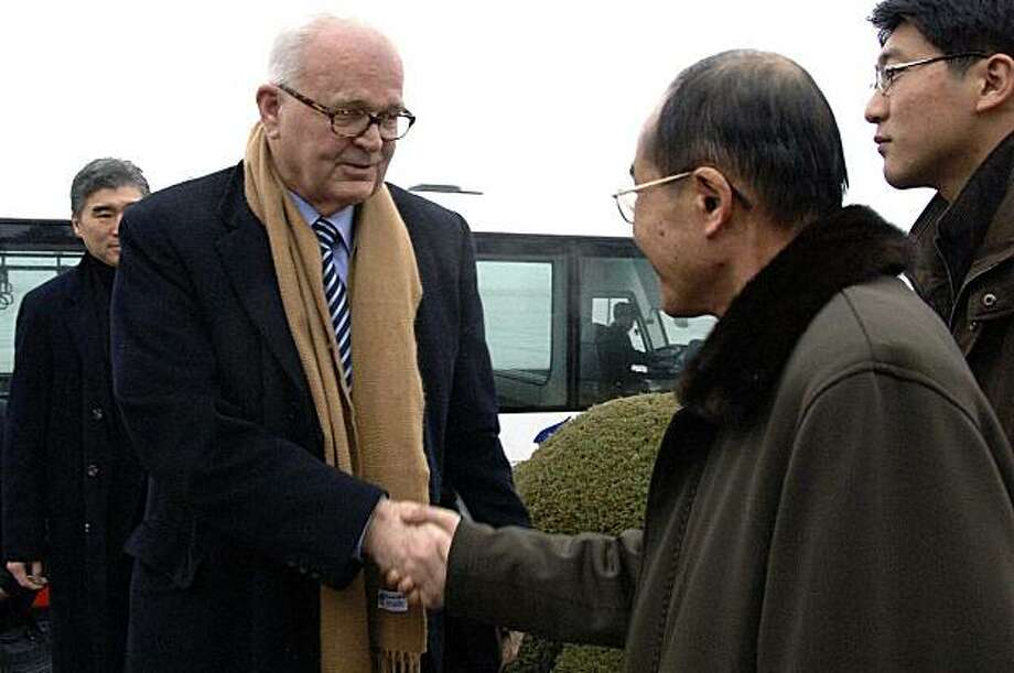 In this photo released by Korean Central News Agency via Korea News Service in Tokyo, U.S. President Barack Obama's special envoy for North Korea, Stephen Bosworth, is welcomed by an unidentified North Korean official, right, upon arrival at Pyongyang airport, North Korea, Tuesday, Dec. 8, 2009. Bosworth began a rare trip to North Korea Tuesday for the highest-level talks with the communist nation in more than a year as a senior U.S. official warned of strong sanctions against Pyongyang unless it rejoins international nuclear talks. (AP Photo/Korean Central News Agency via Korea News Service) ** JAPAN OUT ** Photo: AP