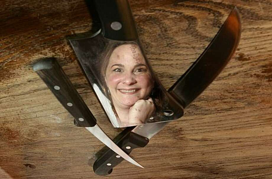 "This photo taken Nov. 23, 2009 shows Julie Powell  reflected in a butchers knife as she poses for a portrait in the Queens borough of New York. Powell is the author of ""Julie and Julia,"" has a new book coming out all about butchering meat called ""Cleaving"".  (AP Photo/Carlo Allegri) Photo: Carlo Allegri, AP"