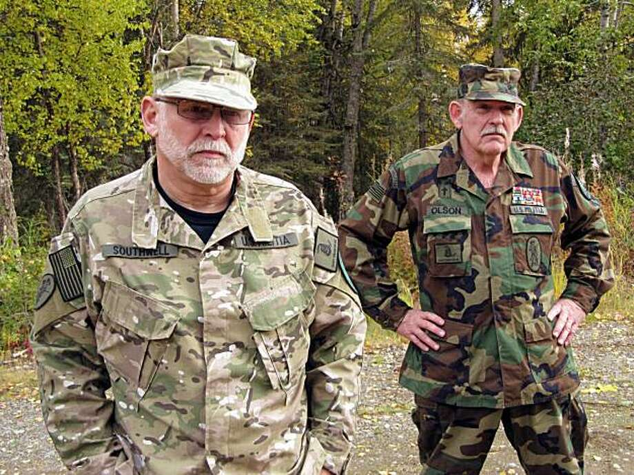 In this photo taken Tuesday Sept. 29, 2009, Ray Southwell, left, and Norm Olson, members of the Alaska Citizens Militia stand by the woods near their home in Nikiski, Alaska. Olson's genial tone belies his reputation as a radical militiaman, yet here he is, at 63, an affable grandfather explaining why Americans should arm themselves against their government. Olson's militia is minuscule at the moment, but there has been a resurgence of the militia movement nationwide, in part coinciding with the advent of the Obama administration. (AP Photo/Rachel D'Oro) Photo: Rachel D'Oro, AP