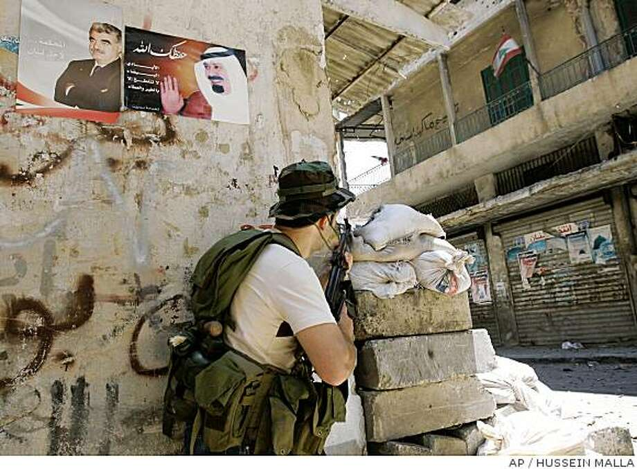 "A Sunni pro-government gunman holds his AK-47 as he takes his position under a two portraits of Slain former Lebanese Prime Minister Rafik Hariri, left, and Saudi's King Abdullah Bin Abdul Aziz , right, with Arabic words reading: ""May God protect you,"" at Bab al-Tabaneh district, in Tripoli, Lebanon, Monday June 23, 2008. Security officials say that heavy overnight fighting between pro- and anti-government supporters in the northern Lebanese city of Tripoli led to the deaths of four more people. The officials say the deaths bring to eight the number of people killed since violence erupted Sunday. Forty-two persons have been wounded so far.(AP Photo/Hussein Malla) Photo: HUSSEIN MALLA, AP"