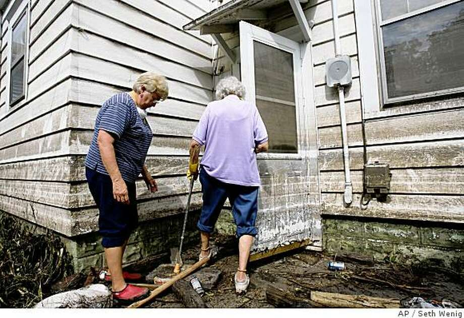 Dorothy Nemecek, right, and her daughter Judy Dolezal try to get a look inside Dorothy's basement in Cedar Rapids, Iowa, Friday, June 20, 2008. Nemecek was trying to clear the way for FEMA inspectors, but because of standing water in the basement and other obstructions, the inspector was unable to complete his assessment. After Hurricane Katrina, many in the flood-stricken Midwest say the agency is doing a good job. (AP Photo/Seth Wenig) Photo: Seth Wenig, AP