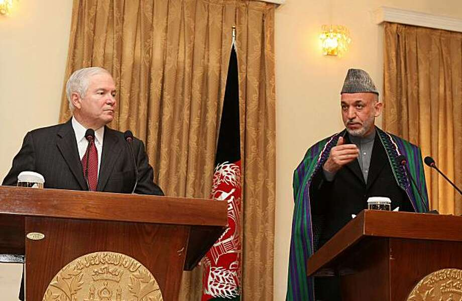 Afghan President Hamid Karzai, right, gestures as U.S. Secretary of Defense Robert Gates looks on during a joint press conference at the presidential palace in Kabul, Afghanistan, Tuesday, Dec. 8, 2009. Gates said that the Afghan security force needs to be strengthened and more soldiers and police need to be recruited to battle militants, but he added that the U.S. is committed to help Afghanistan for the long haul. (AP Photo/Justin Sullivan, Pool) Photo: Justin Sullivan, AP