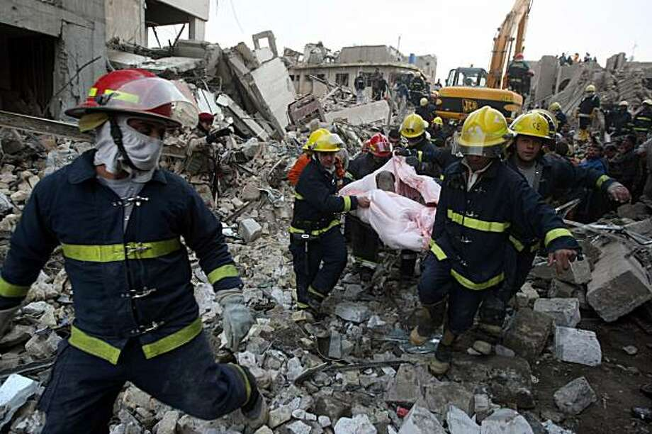 Iraqi rescue workers evacuate a body at the scene of a bomb blast near the Finance Ministry in Baghdad on December 7. Five massive vehicle-borne bombs rocked Baghdad, killing 127 people, including women and students, and wounding hundreds. Photo: Ahmad Al-Rubaye, AFP/Getty Images