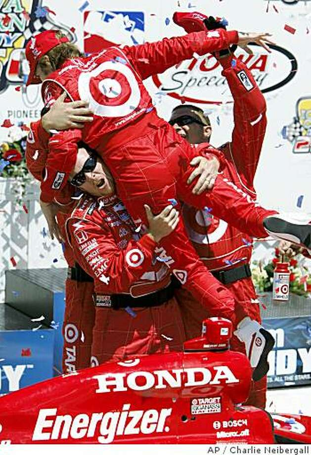 Dan Wheldon, top, celebrates with crew members after winning the IndyCar Series' Iowa Corn Indy 250 auto race Sunday, June 22, 2008, at the Iowa Speedway in Newton, Iowa. Photo: Charlie Neibergall, AP