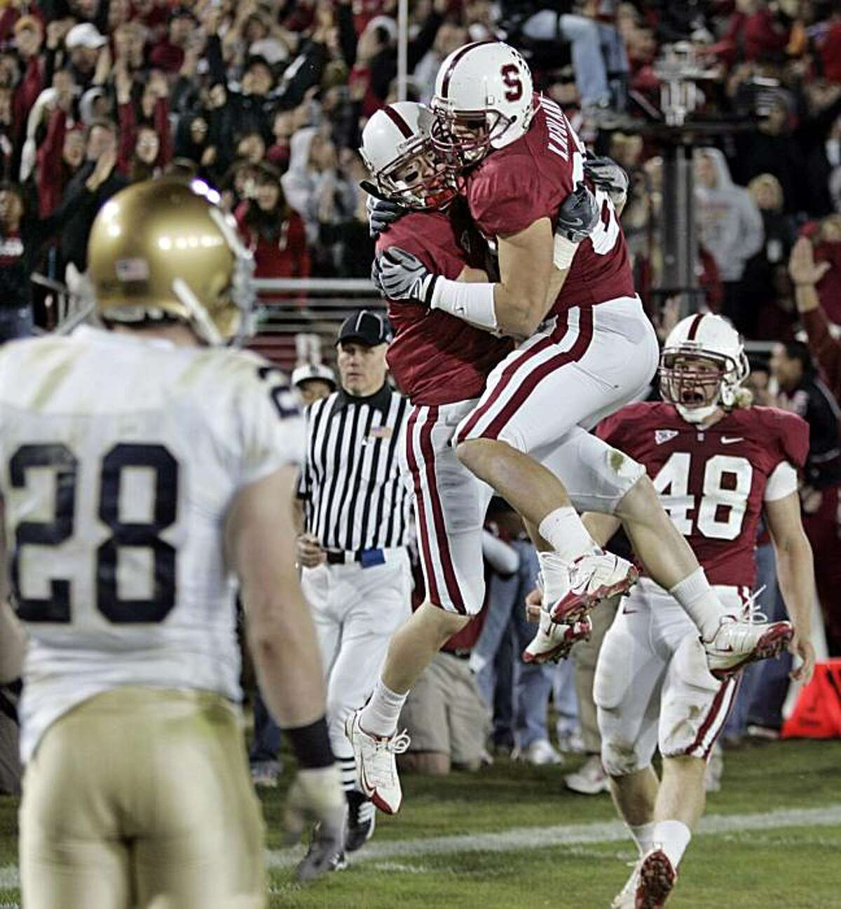 Stanford wide receiver Ryan Whalen, left, is congratulated by tight end Konrad Reuland, right, after scoring in front of Notre Dame safety Kyle McCarthy (28) in the fourth quarter of their NCAA college football game in Stanford, Calif., Saturday, Nov. 28, 2009. Stanford defeated Notre Dame 45-38. (AP Photo/Paul Sakuma)