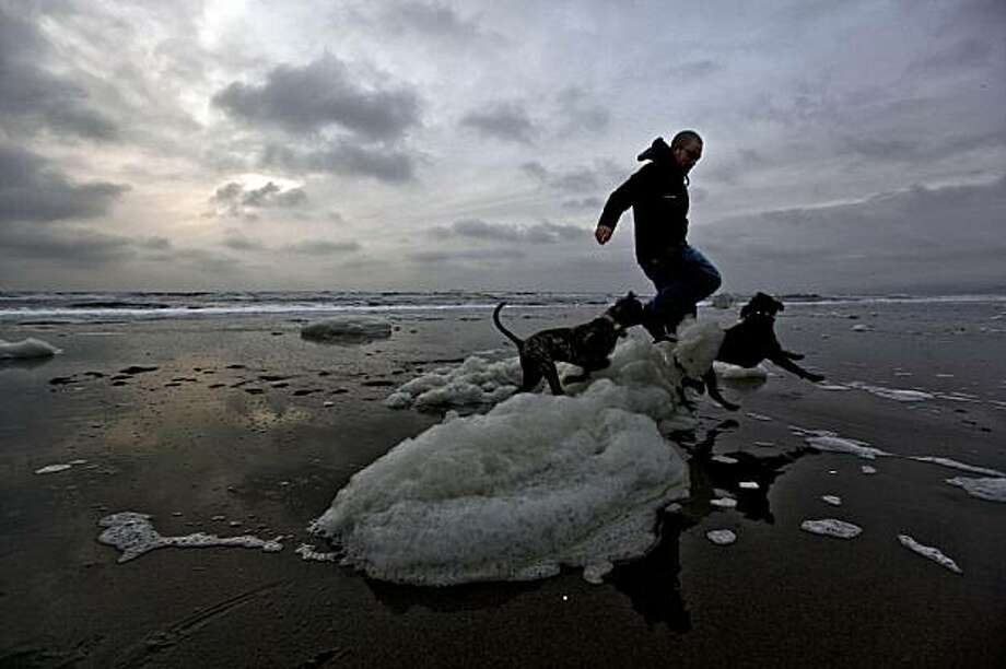 "Alan Rodriguez, of San Francisco, hurdles a little beach foam with his dogs, ""Bruiser"" (left) and ""Oynx"" along ocean beach towards the end of the day as thick cloud cover rolls onshore on Friday December 4, 2009. Photo: Michael Macor, The Chronicle"