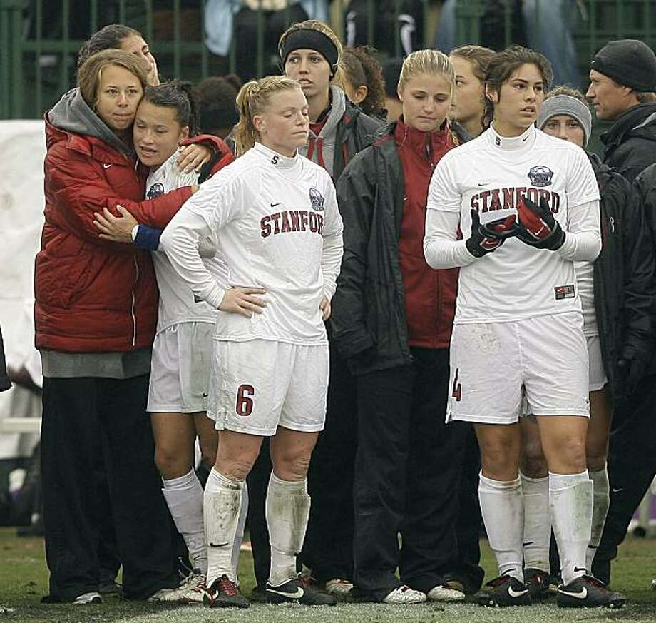 Stanford's Alicia Jenkins left, and Alina Garciamendez watch as North Carolina celebrates their win during the NCAA college women's soccer championship final, on Sunday, Dec. 6, 2009, in College Station, Texas. North Carolina won 1-0.  (AP Photo/Bob Levey) Photo: Bob Levey, AP