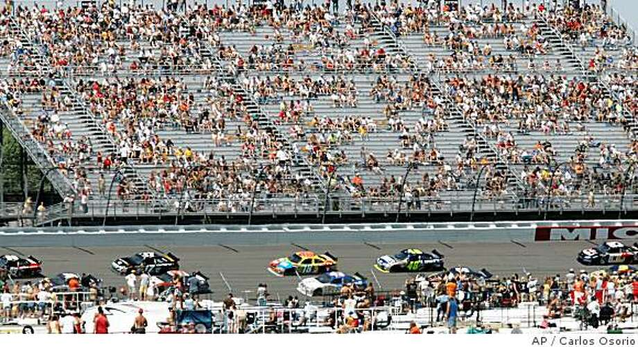 A sparse crowd watches NASCAR Sprint Cup Series drivers in the LifeLock 400 at Michigan International Speedway in Brooklyn, Mich., Sunday, June 15, 2008. At a track where NASCAR used to regularly draw about 160,000 spectators, Sunday's crowd was noticeably smaller. Track officials gave no crowd estimate but published reports said up to 30,000 fewer tickets were sold than for the race last June, thanks to high gas prices and the depressed Michigan economy. (AP Photo/Carlos Osorio) Photo: Carlos Osorio, AP
